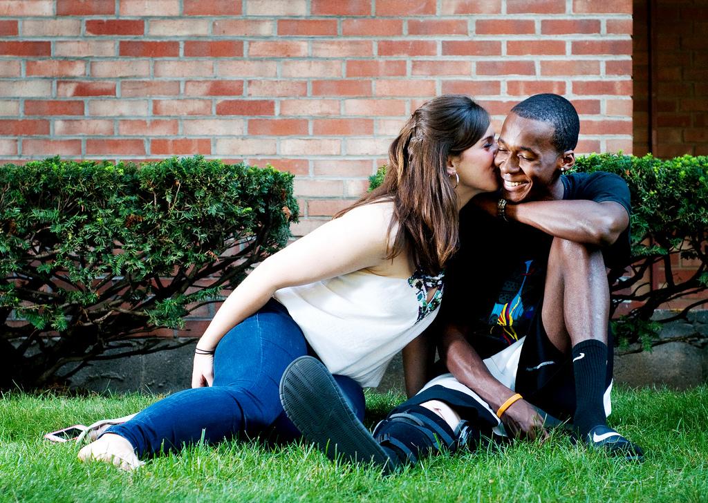 Interracial couple embracing having fun outdoors photos